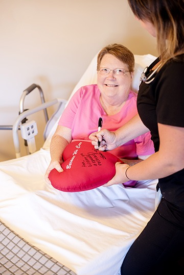 Patient Holding An Original Heart Pillow Thats Being Signed By A Nurse